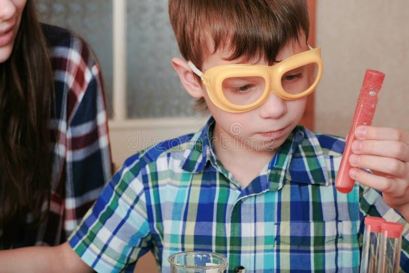 De chemie experimenteert thuis Het mamma en de zoon maken een chemische reactie met de versie van gas in de reageerbuis met rood stock foto's