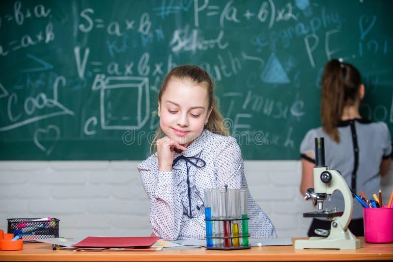 De chemische reacties van microscoopreageerbuizen Leerlingen bij bord Fascinerende wetenschap Formeel onderwijsschool stock foto