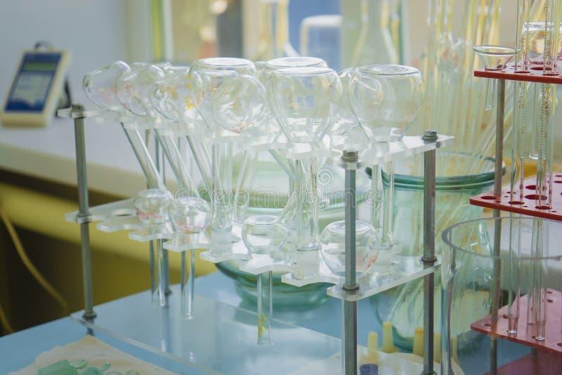 De chemische test van het glaslaboratorium in overlappingsruimte Retro laboratoriummateriaal en boeken dichtbij verlichtingskaars royalty-vrije stock afbeeldingen