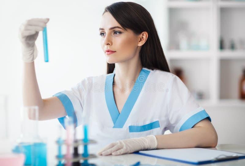 De chemische vrouwelijke fles van de onderzoekersholding in laboratorium stock foto