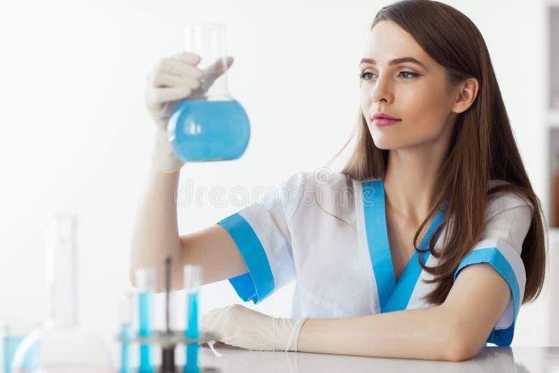 De chemische vrouwelijke fles van de onderzoekersholding in laboratorium royalty-vrije stock afbeelding