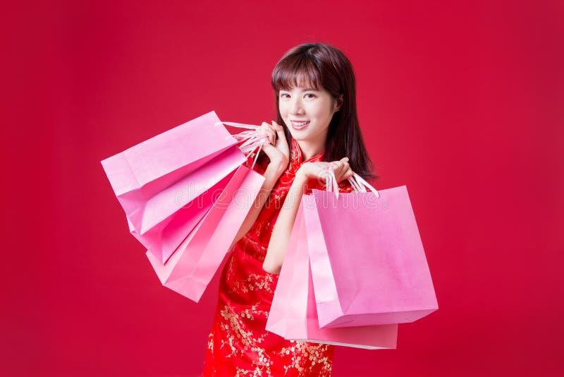 De Cheongsamvrouw toont het winkelen zakken stock afbeelding
