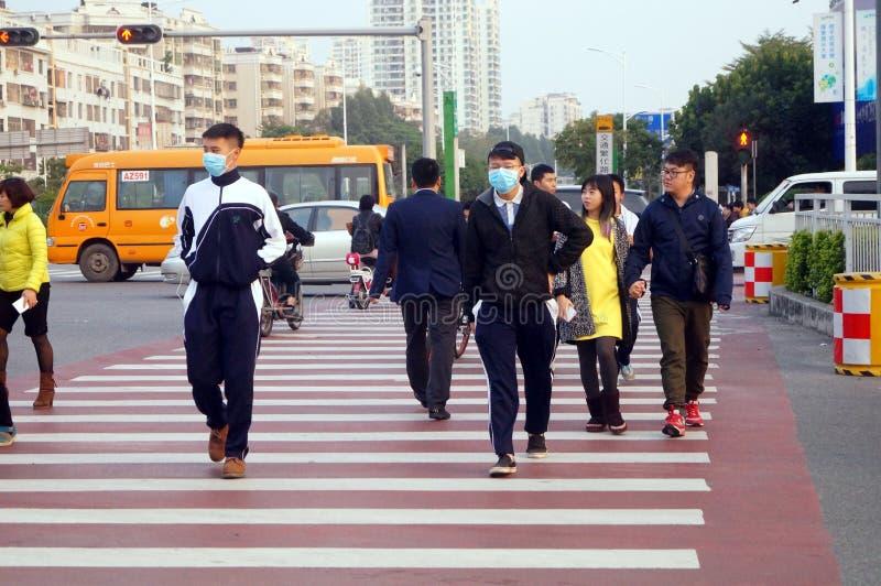 De Chinese lage schoolstudenten kruisen de weg en slijtagemaskers stock fotografie