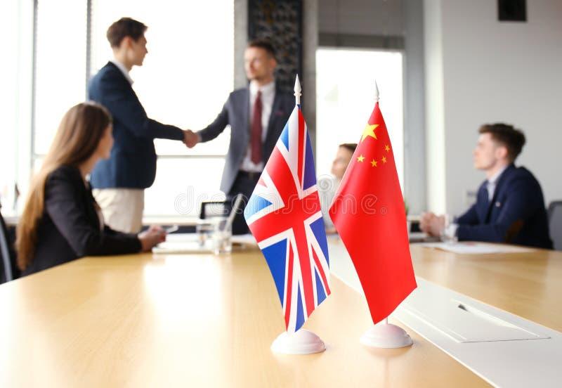 De Chinese leiders die van het Verenigd Koninkrijk en handen op een overeenkomstenovereenkomst schudden royalty-vrije stock foto