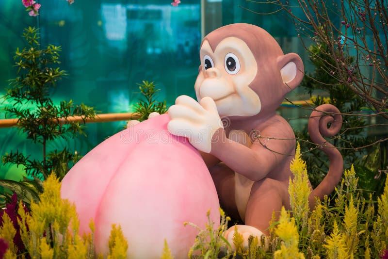 De Chinese mascotte van de Nieuwjaaraap met perzik stock foto's