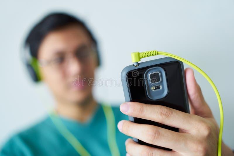 De Chinese Mens met Groene Hoofdtelefoons luistert de Telefoon van Muziekpodcast royalty-vrije stock foto