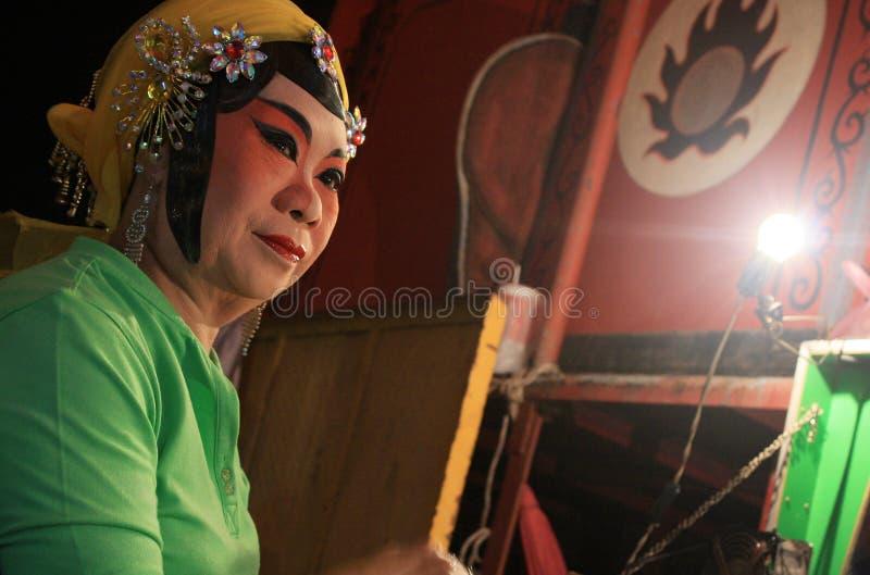 De Chinese operaactrice schildert masker op zijn gezicht bij nacht royalty-vrije stock afbeelding