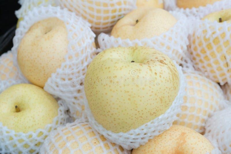 De Chinese peren wraped door netto plastiek op verkoop in supermarkt stock foto's