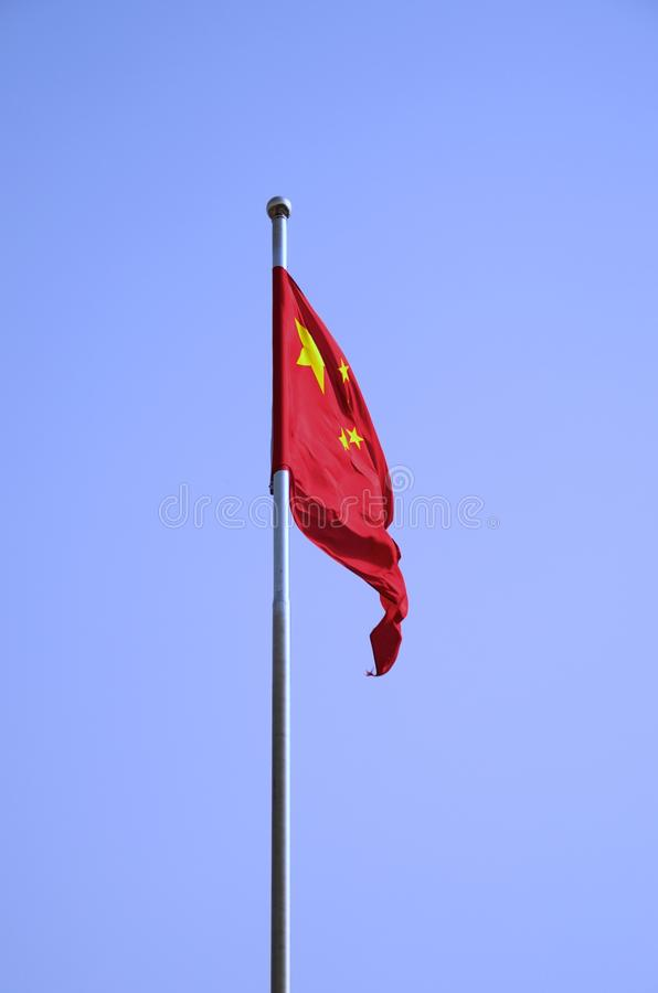 De Chinese Vlag die tegen een Stevige Blauwe Hemel klappen stock afbeeldingen