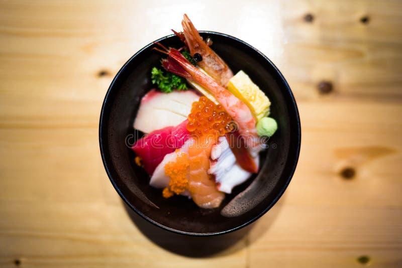 De Chirashisushi, de Japanse kom van de voedselrijst met ruwe zalmsashimi, gemengde zeevruchten, hoogste die mening, verdonkeren  stock foto