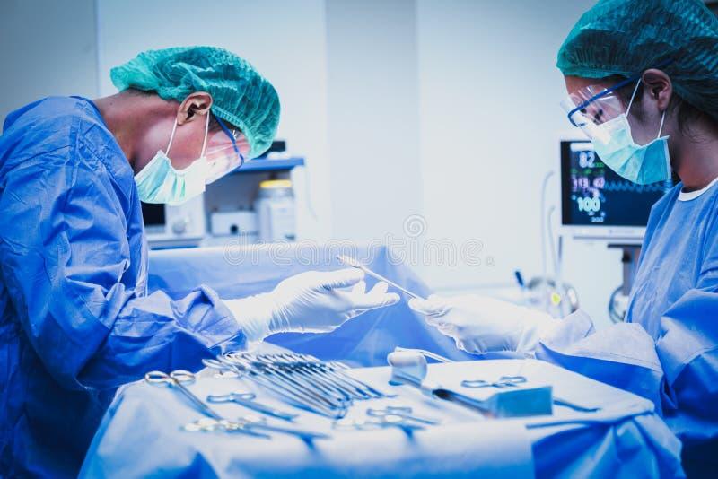 De chirurg en de medewerker werken in de werkende ruimte stock fotografie