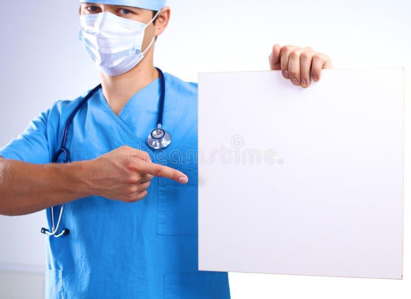 De chirurg in het masker houdt een aanplakbiljet stock afbeelding