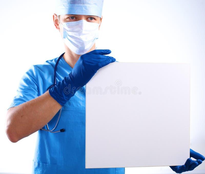 De chirurg in het masker houdt een aanplakbiljet royalty-vrije stock foto