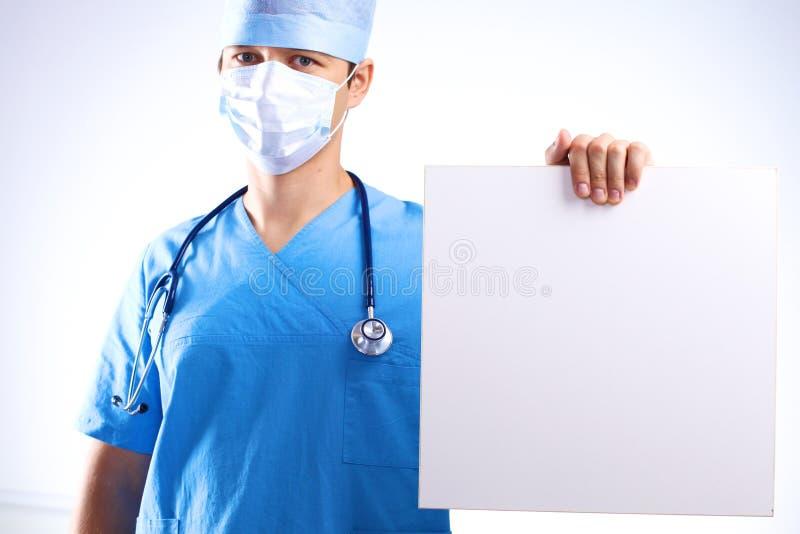 De chirurg in het masker houdt een aanplakbiljet royalty-vrije stock foto's