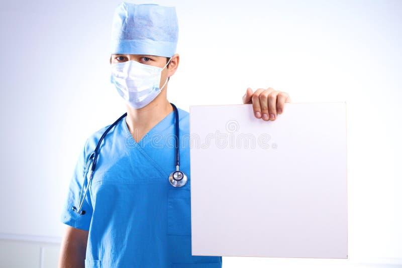 De chirurg in het masker houdt een aanplakbiljet stock fotografie