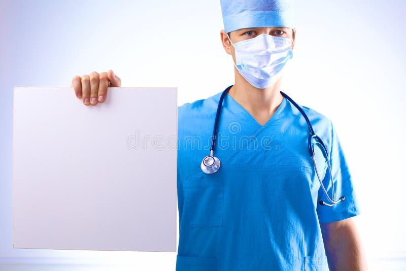 De chirurg in het masker houdt een aanplakbiljet stock afbeeldingen