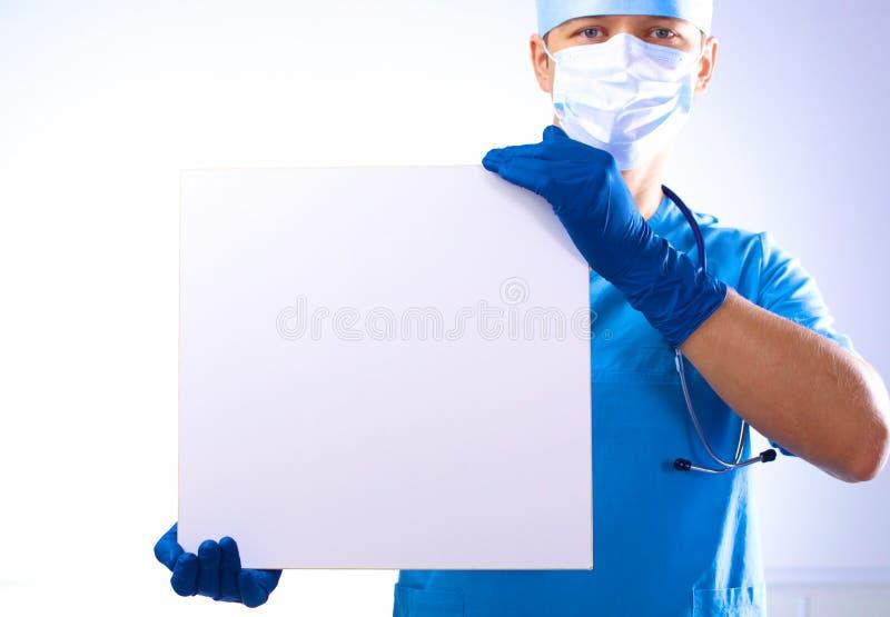 De chirurg in het masker houdt een aanplakbiljet royalty-vrije stock fotografie