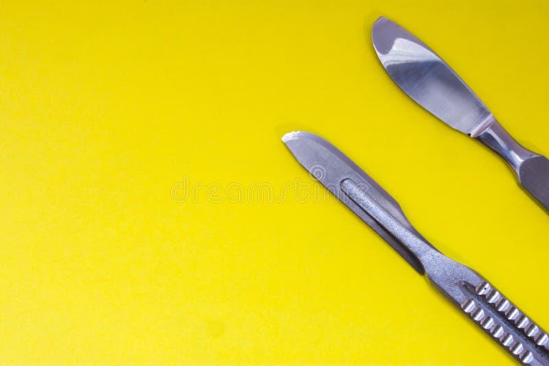 Is de chirurgische scalpel van het twee metaalchroom op een gele achtergrond met ruimte voor tekst en rubrieken Fotoillustratie i stock foto's