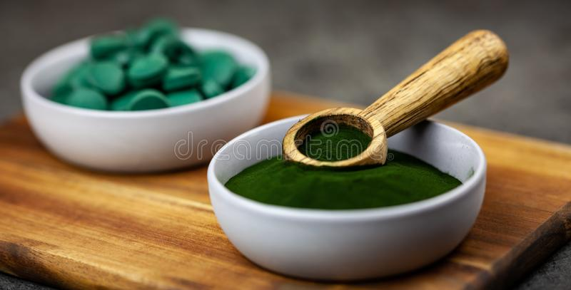 De chlorella, de spirulina groene algen in poeder en de tabletten vormen close-up, macroschot stock foto