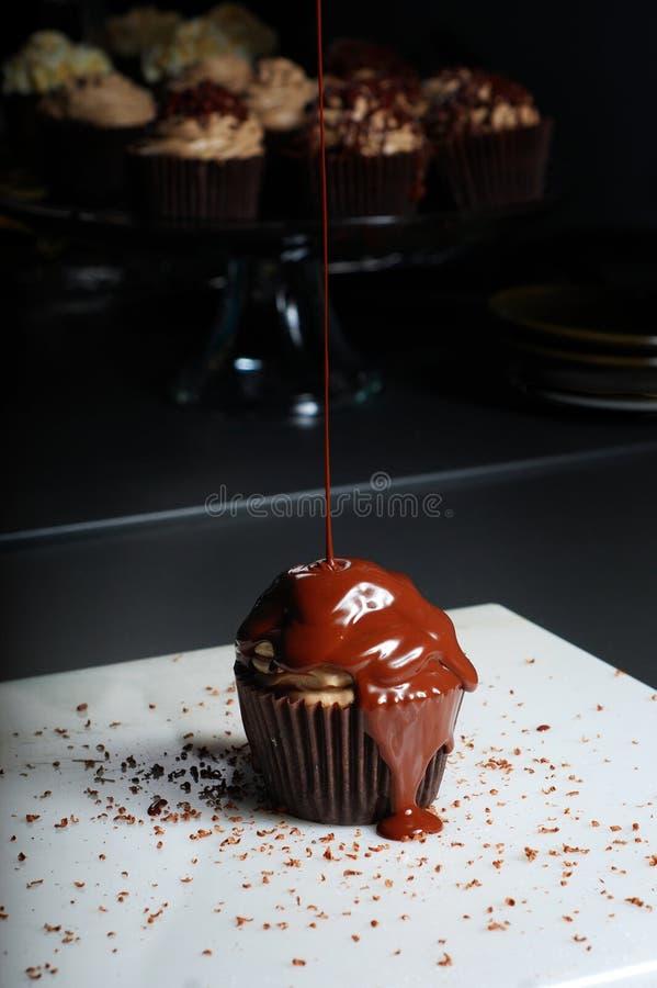 De chocolade cupcake motregende met chocoladesaus stock fotografie