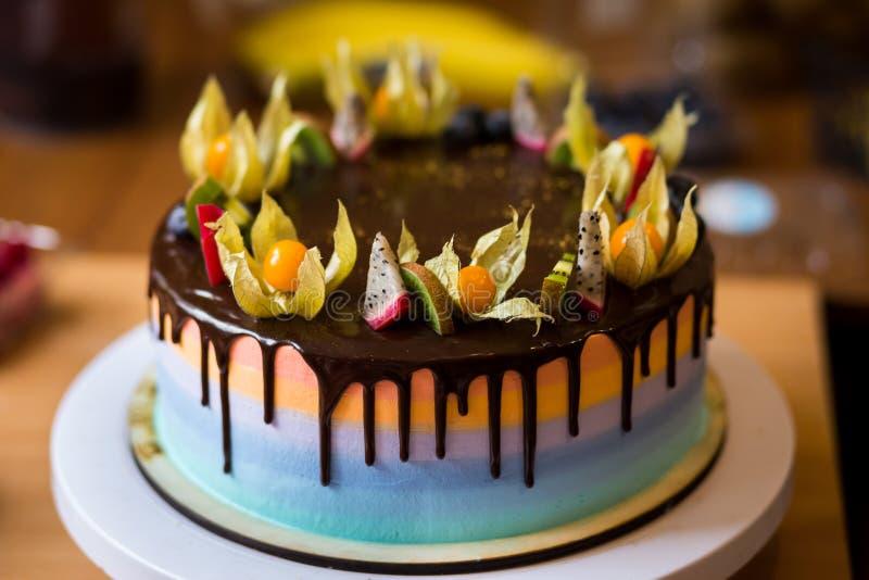 De chocolade cupcakes met gekleurde die lagen, met fruit worden verfraaid, is stock afbeeldingen
