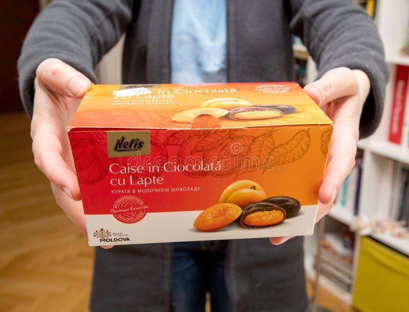 De chocolade van de Nefisabrikoos met melk in de hand van de vrouw royalty-vrije stock afbeeldingen