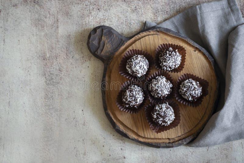 De chocoladecakes bestrooien kokosnoot in pakpapiervormen op een houten Raad royalty-vrije stock fotografie