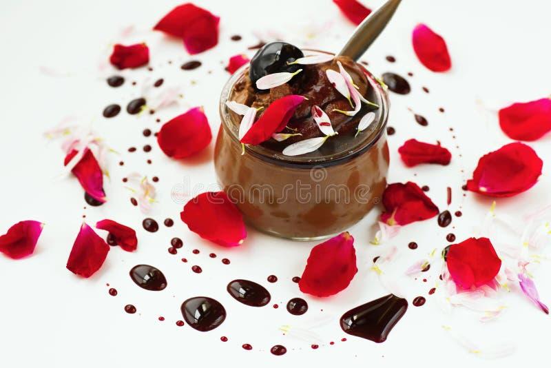 De chocolademousse, nam blad, stroopdaling op achtergrond toe stock afbeelding