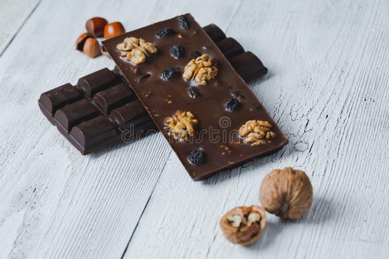 De chocoladereep met notenclose-up wordt gevuld ligt oude houten lijst w dat stock fotografie