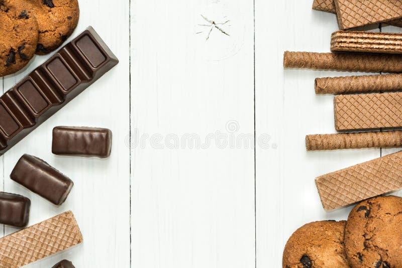 De chocoladesnoepjes, chocoladewafel rolt, koekjes op een houten witte lijst, ruimte in het centrum voor tekst stock afbeeldingen