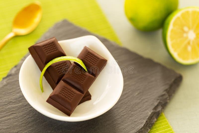 De chocoladestukken met kalk pellen in een kom op een lei, met een kalk en een gouden lepel over een groene lijstmat en een groen royalty-vrije stock afbeeldingen