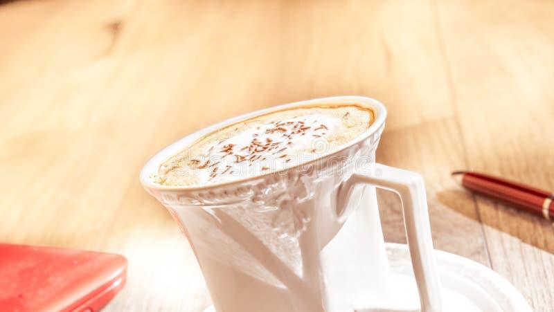 De de chocoladevlokken en melk schuimen - kop van cappuccinokoffie op uitstekende houten lijst stock foto's