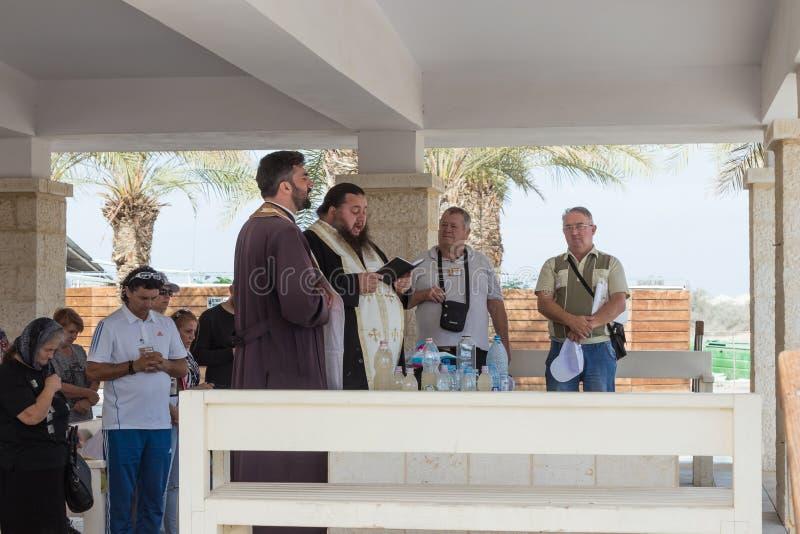 De christelijke priesters bidden in aanwezigheid van gelovigen op de toeristenplaats Qasr Gr Yahud in Israël stock fotografie