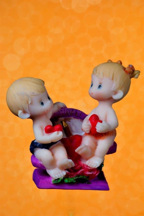 De cijfers van de minnaars zijn de kinderen op de schommeling, gouden ontwerp als achtergrond St Valentine de dag is een vakantie stock afbeeldingen