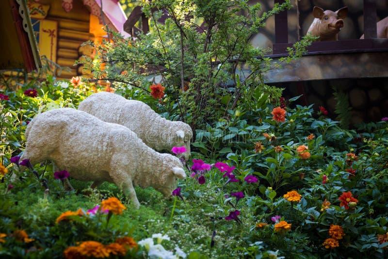 De cijfers van twee witte schapen De dieren weiden in een weide van bloemen Een prachtige tuin, de milieuvriendelijke landbouw, royalty-vrije stock afbeeldingen
