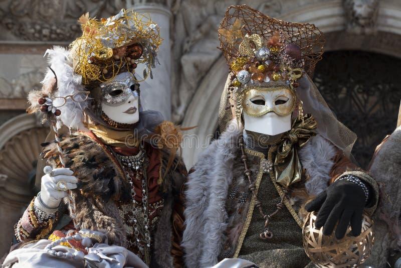 De Cijfers van Venetië Carnaval in kleurrijke gouden en bruine kostuums en maskers Venetië Italië royalty-vrije stock foto
