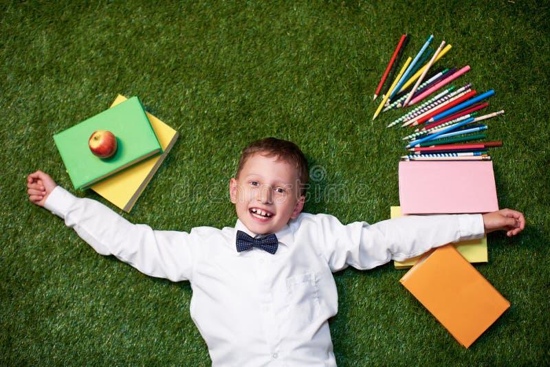 De cima de um menino com cadernos encontra-se na grama e nos sorrisos o estudante encontra-se com livros e lápis no gramado imagens de stock