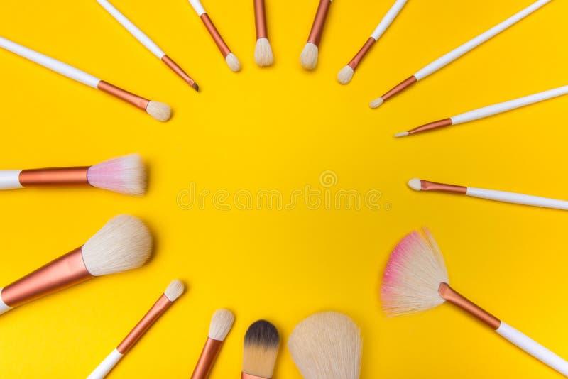 De cirkel van make-upborstels op gele achtergrond stock fotografie