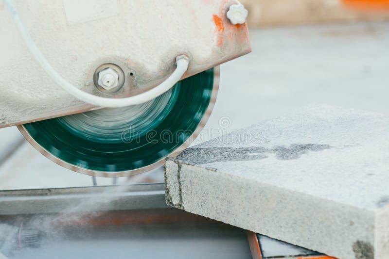 De cirkelzaag snijdt een brok graniettegels voor bestrating stock foto's