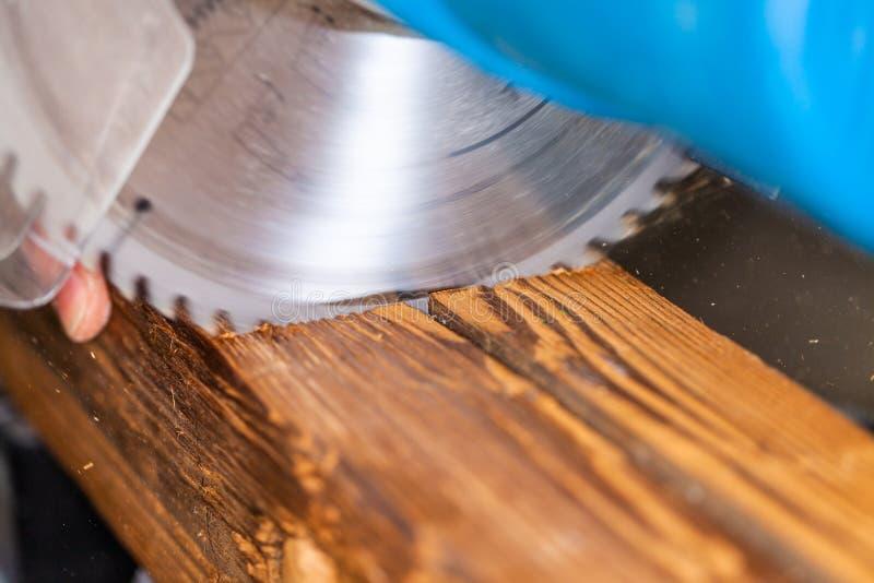 De cirkelzaag snijdt een hout stock fotografie