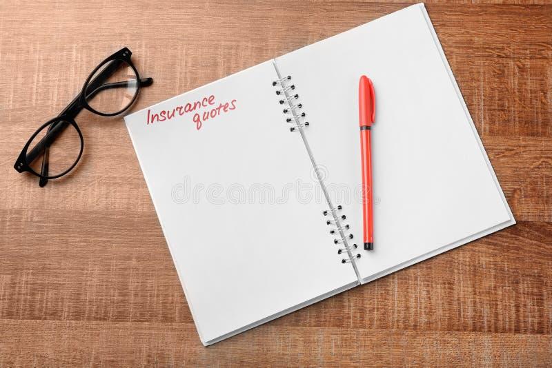 De CITATEN van de tekstverzekering in notitieboekje worden geschreven dat stock afbeelding