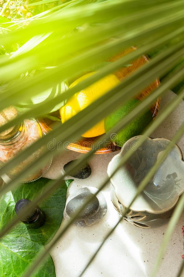 De citroenkalk in het houten van het de flessen groene palmblad van de kometherische olie zout van Himalayan roze bracht zen sten royalty-vrije stock afbeeldingen