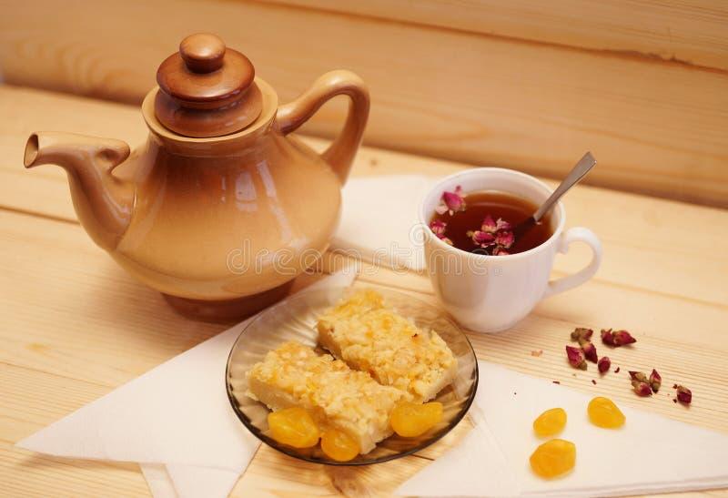 De citroenpastei op een plaat ligt naast een kop thee en een ketel stock afbeelding