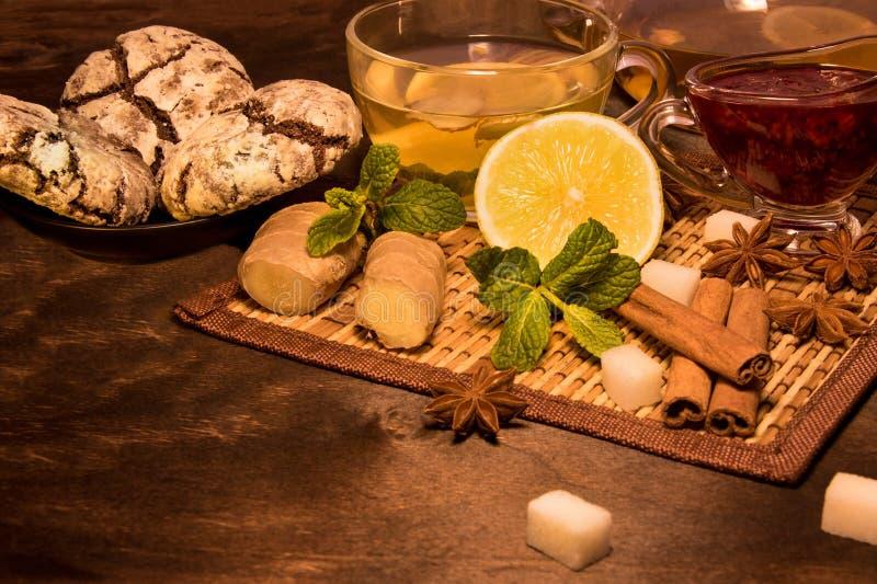 De citroenthee met transparante mok en de theepot een munt en een framboos blokkeren, gemberglas en cinnamobrouwerij en chocolade stock afbeelding