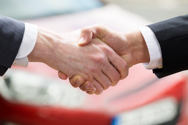 De Cliënt van verkopersshaking hands with na het Verkopen van Auto stock foto