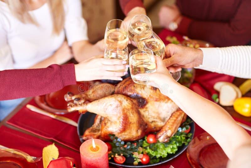 De clinking glazen van de close-upfamilie op Dankzegging op een lijstachtergrond Toejuichingen met champagne Het concept van de v stock afbeelding