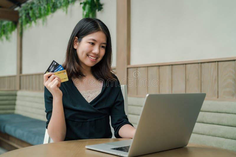 De close-up de Aziatische mooie vrouw die een zwarte overhemdszitting in het huis dragen een creditcard heeft koopt ter beschikki royalty-vrije stock foto's
