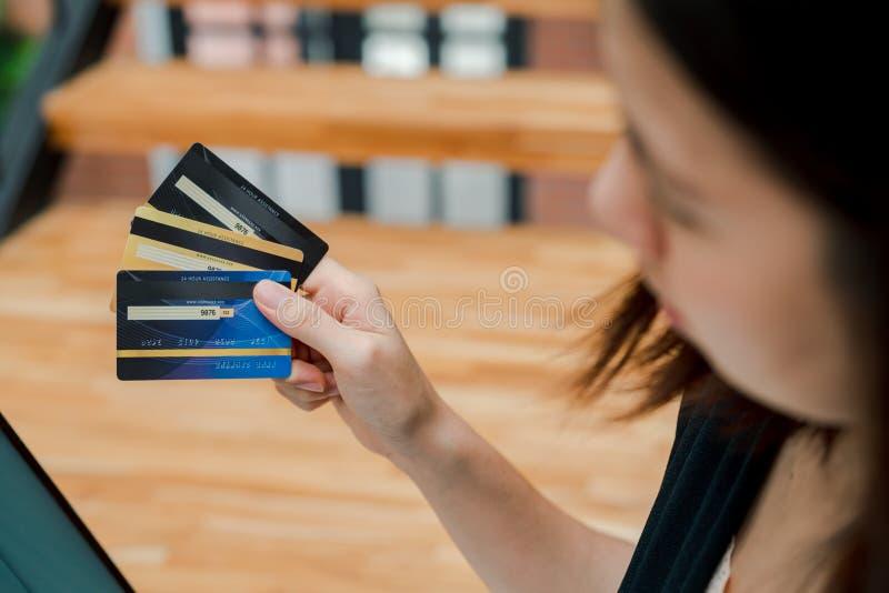 De close-up de Aziatische mooie vrouw die een zwarte overhemdszitting in de treden in het huis dragen een creditcard heeft koopt  royalty-vrije stock foto's