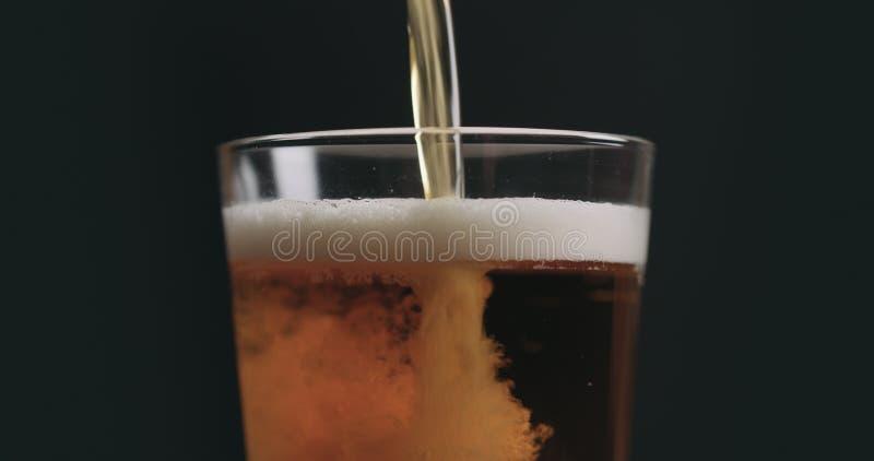 De close-up giet licht aalbier in pintglas over zwarte achtergrond royalty-vrije stock afbeelding