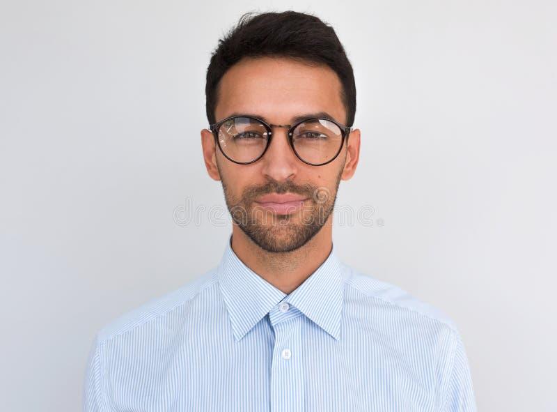 De close-up headshot van knap aantrekkelijk die mannetje, bekijkt direct de camera, draagt om bril, over witte achtergrond wordt  stock afbeeldingen